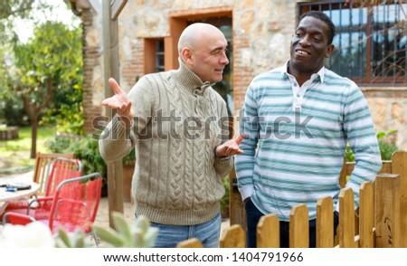 Good neighbors talk on the border of their farms #1404791966