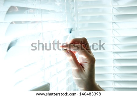 Someone looking out of window opening blinds #140483398