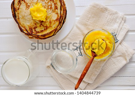 A stack of homemade pancakes on a white plate on a light wooden table. Pancakes are served with GHEE oil. This oil is very healthy. Copy space. Rustic. #1404844739