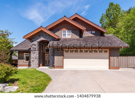Beautiful exterior of newly built luxury home. Yard with green grass and stone. #1404879938