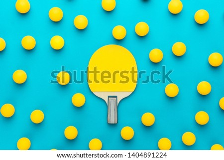 racket and many balls for table tennis on turquoise blue background. flat lay image of many table tennis balls with tennis paddle in the middle. minimalist photo of yellow ping-pong equipment #1404891224