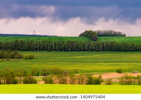 Beautiful landscape, green and yellow field. Dramatic sky with clouds. #1404975404