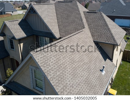 Residential shingle roof using ridge vent s with gables visible Royalty-Free Stock Photo #1405032005