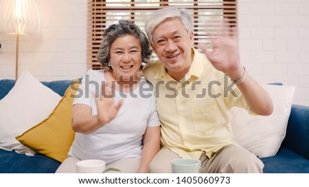 Asian elderly couple using smartphone video conference with grandchild while lying on sofa in living room at home. Enjoying time lifestyle senior family at home concept. Portrait looking at camera. #1405060973