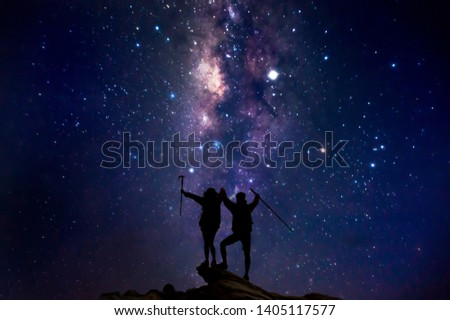 Landscape with Milky Way. Night sky with stars and silhouette of a couples happy hikers climbing up mountain cliff on the mountain. #1405117577