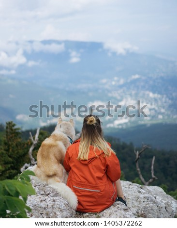 Young female sitting with siberian husky dog in mountains, Gorgeous Siberian Husky dog ​​standing on a rock in the mountains. view of the sea. #1405372262