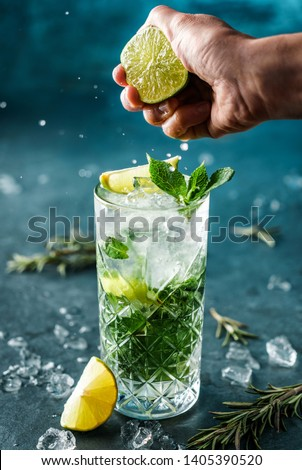 Fresh Mojito cocktail with lime, rosemary, mint and ice in jar glass on dark blue background. Man hand squeezes lime juice from mojito cocktail with splash and drops. Summer cold drink and cocktail #1405390520