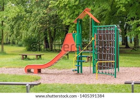 Empty playground after rain. Slide got wet in raindrops. Summer or spring rainy day. No people. No children. #1405391384