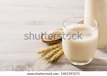 Oats milk in bottle and glass on wooden table. Copyspace #1405393271