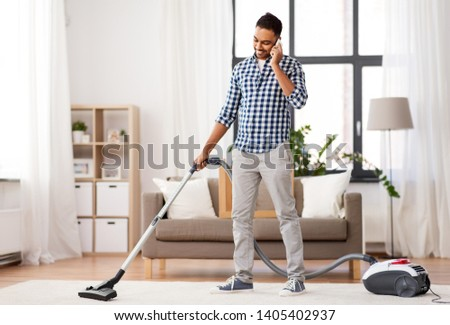 household and cleaning concept - indian man with vacuum cleaner calling on smartphone at home #1405402937