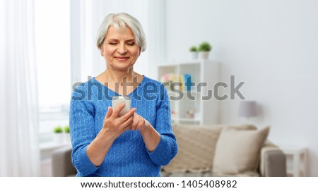 technology and old people concept - smiling senior woman using smartphone over home background #1405408982