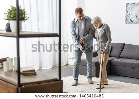 full length view of man helping senior mother with cane at home #1405410485