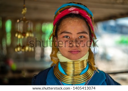 Young smiling Asian long-neck Kayan Padaung woman in traditional costume. Ethnic minority in Asia. Beautiful portrait of tribal woman with neck rings brass coils in Loikaw, Myanmar. #1405413074