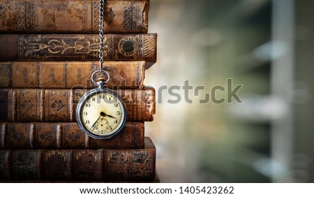 Vintage clock hanging on a chain on the background of old books. Old watch as a symbol of passing time. Concept on the theme of history, nostalgia, old age. Retro style. Royalty-Free Stock Photo #1405423262