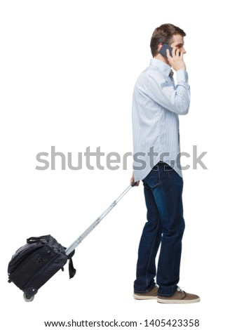 Side view of walking business man with suitcase talking on the phone. Standing young girl. Rear view people collection.   Isolated over white background. A young businessman at the airport calls #1405423358