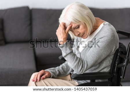 sad disabled senior woman on wheelchair at home #1405437059