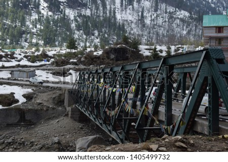 dark rocky mountains with snow over them in himachal pradesh india in winters with blue sky and clouds with a old metal bridge in forground #1405499732