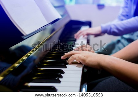 A boy is learning piano with woman teacher and music notation, four hands from two people playing piano, there are musical instrument for learning music, the music learning concept, selective focus. #1405510553