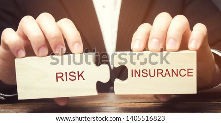 Businessman collects wooden puzzles with the word Risk insurance. The transfer of certain risks to the insurance company. Banking and credit risks. Business and finance. Property / accident.