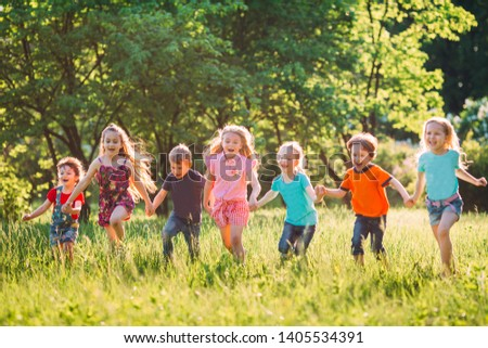 Large group of kids, friends boys and girls running in the park on sunny summer day in casual clothes  #1405534391