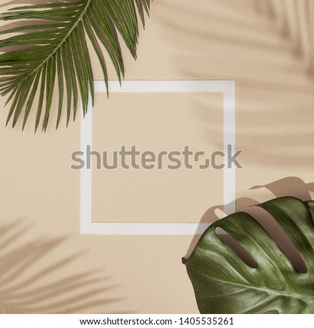 Top view of green tropical leaves and shadows on sand color background. Flat lay. Minimal summer concept with palm tree leaf. Creative copyspace with paper frame. #1405535261