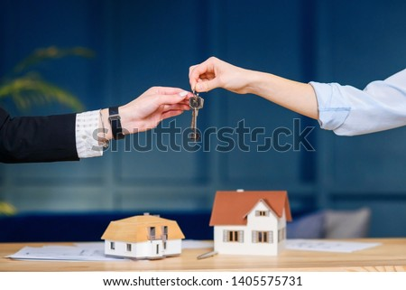 Close up shot of female realtor hands giving keys from the new flat, house to female clients. #1405575731