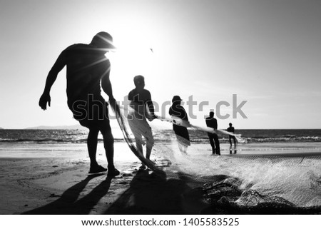 Aceh, Indonesia - February 2017: Life of traditional fishermen on the beach. Human fishermen pull nets from the sea in the morning sun. Fishing in Aceh is the main industry in its coastal countries. #1405583525