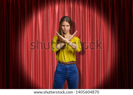 Young determined woman wearing jeans and yellow shirt making rejection gesture on red stage curtains background. Digital art. Feelings and emotions. People and objects. #1405604870