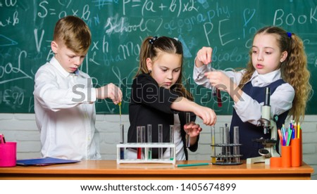 Study of liquid states. Group school pupils study chemical liquids. School laboratory. Girls and boy conduct experiment with liquids. Teamwork concept. Test tubes with colorful liquid substances. #1405674899