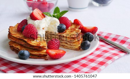 Stack of keto pancakes made of coconut flour or almond flour, served with berries and whipped cream on plate. One slice eaten already. #1405761047