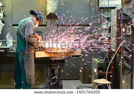 workers in safety clothing sanding a casting in an industrial company  #1405764200