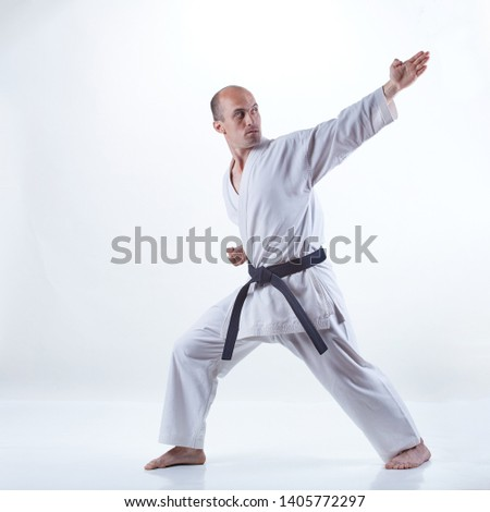 Young athlete in karategi doing formal karate exercises on a light background #1405772297