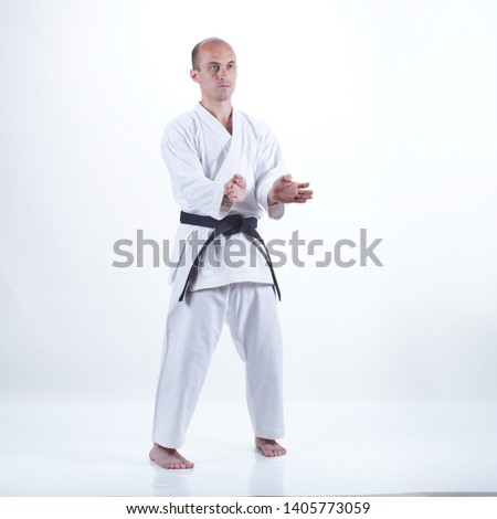 On a light background, a young active athlete does formal karate exercises  #1405773059