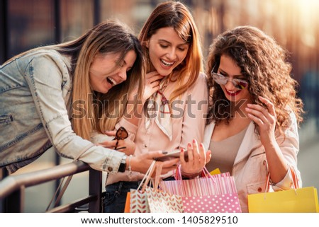 Three beautiful young women with shopping bags in the city.Sale,fashion,consumerism and people concept #1405829510