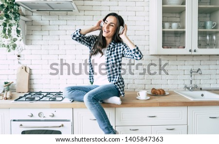 Relax at home. Beautiful happy young woman in headphones is listening music and have a fun on the kitchen. #1405847363