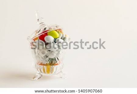 Colorful almond candies in the stylish,crystal candy bowl on white with copy space.The Sugar Feast concept. #1405907060