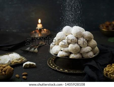 Cookies for celebration of El Fitr Islamic Feast( The Feast that comes after Ramadan).Sprinkling powdered sugar on Kahk (Eid-Al- Fitr cookies). #1405928108