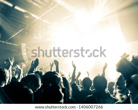 Concert crowd clapping a band on the lit stage #1406007266