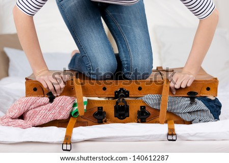 Midsection of young woman packing suitcase on bed Royalty-Free Stock Photo #140612287