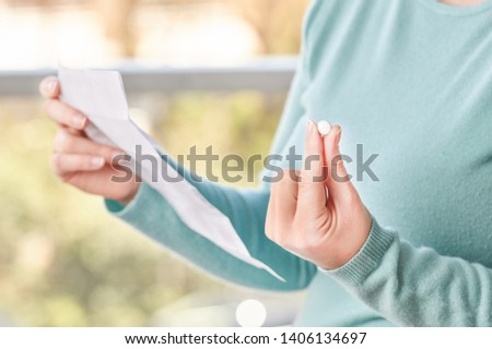Shot of an unrecognizable young woman hands holding a pill and reading a leaflet  #1406134697