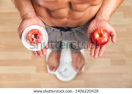 Diet. Woman Measuring Body Weight On Weighing Scale Holding Donut and apple. Sweets Are Unhealthy Junk Food. Dieting, Healthy Eating, Lifestyle. Weight Loss. Obesity. Top View #1406220428