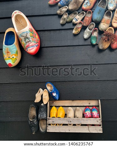 Beautiful Dutch wooden shoes, traditional wooden clogs are showing on the black wooden wall at ZAANSE SCANE , HOLLAND. #1406235767