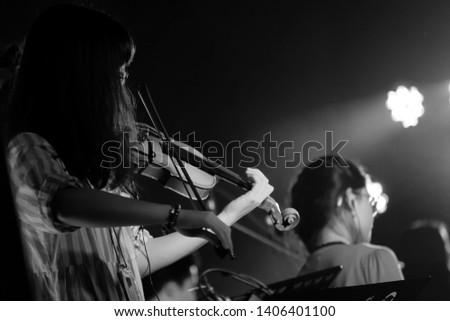 Young Violinist Girl Performance with Her Violin iNstrument on the indoor Concert Stage. Black and White. #1406401100