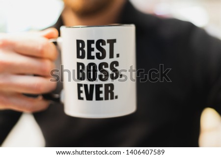 A man holding a coffee mug with best boss ever printed on it. #1406407589