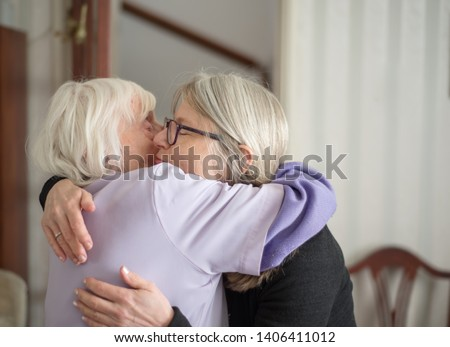 After a visit to see her elderly and sight impaired mother,the daughter hugs and says goodbye to her mom, before her long drive back home. #1406411012