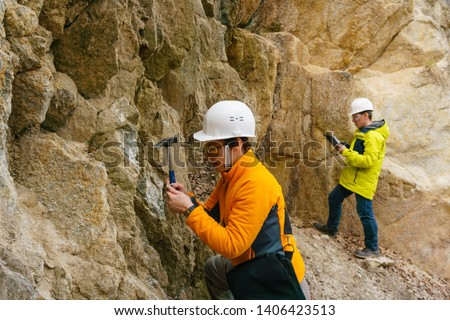 male and female geologists takes a sample of the mineral and record data in a canyon #1406423513