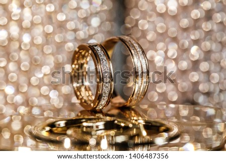 Pair of gold wedding rings with bokeh background #1406487356