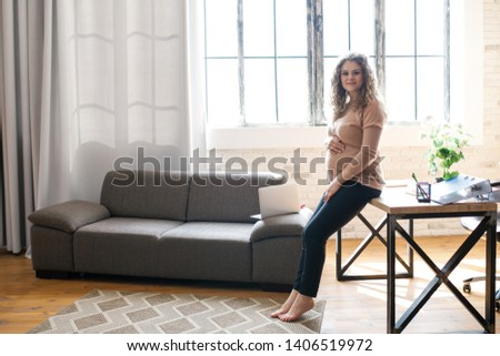 Beautiful pregnant woman working behind a laptop sitting on the sofa. The happiest time for every woman #1406519972