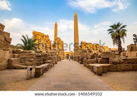 EXPLORING EGYPT - KARNAK TEMPLE - Travel tour group wanders through Karnak Temple. Beautiful Egyptian landmark with hieroglyphics, decayed temples, obelisks, towers, and other buildings. Luxor, Egypt #1406549102