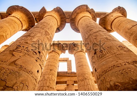 EXPLORING EGYPT - KARNAK TEMPLE - Massive columns inside beautiful Egyptian landmark with hieroglyphics, and ancient symbols. Famous landmark in the world near the Nile River and Luxor, Egypt Royalty-Free Stock Photo #1406550029